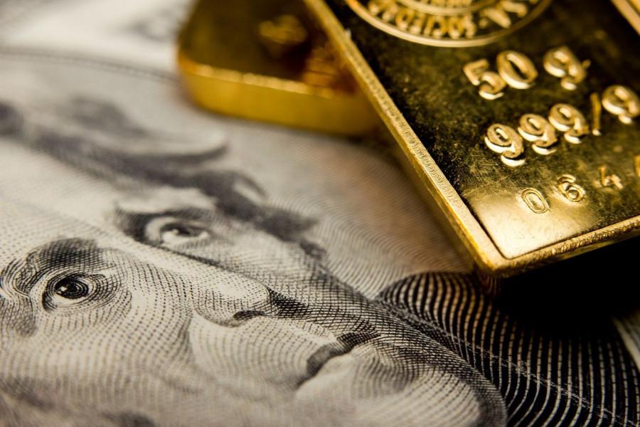Цены на золото снизились впервые за 3 сессии под давлением сильного доллара